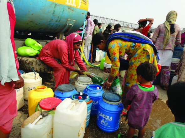 Women and children collect drinking water from tanks at an urban resettlement slum in Delhi, India