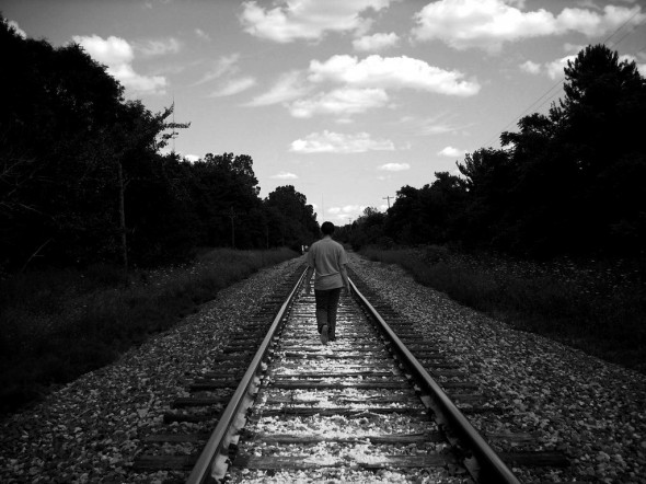 Person walking alone on train tracks